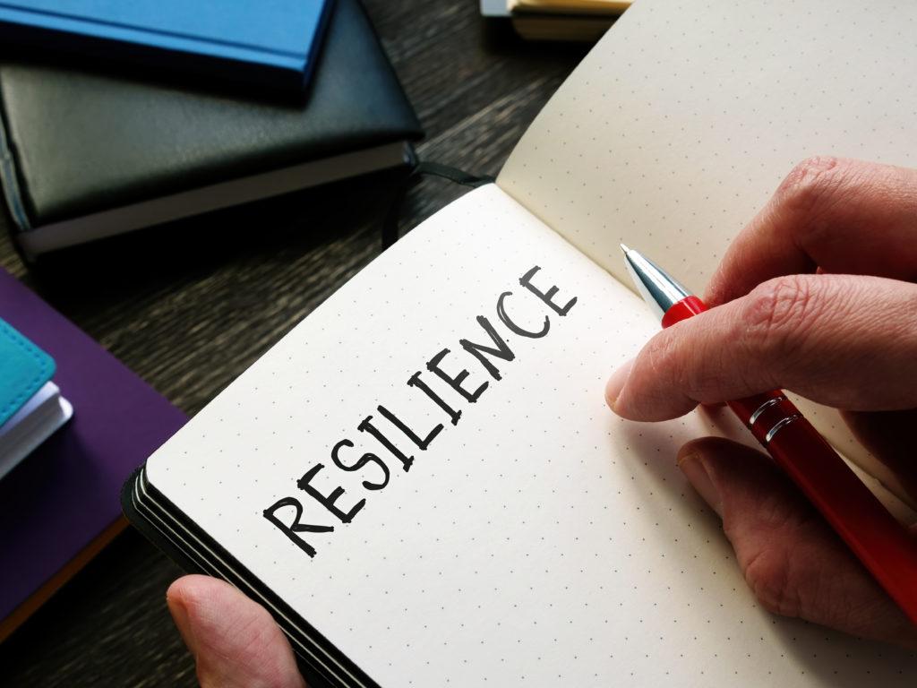 Image avec des petits cahiers sur une table. On voit au premier plan un cahier ouvert tenu par des mains. Le mot résilience est écrit à l'encre noir, comme le titre de l'article.